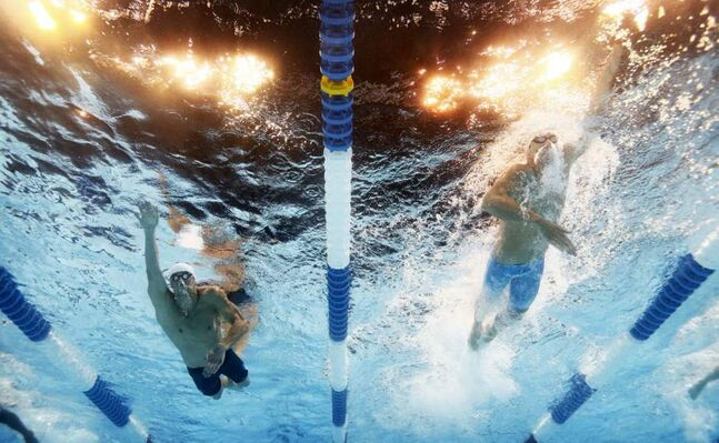 Michael Phelps, left, and Conor Dwyer swim in the men's 200-meter freestyle preliminaries at the U.S. Olympic swimming trials. (AP Photo/Mark J. Terrill)