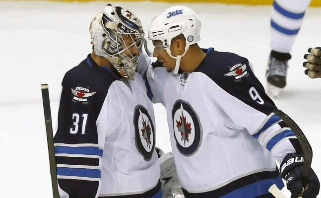 Winnipeg Jets goalie Ondrej Pavelec is congratulated by teammate Evander Kane after the win against the Detroit Red Wings.