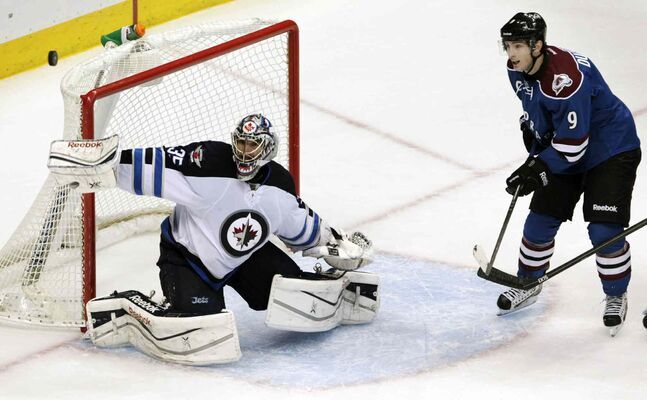 With his stick in his own net, Winnipeg Jets goalie Al Montoya (left) blocks a shot as Colorado Avalanche center Matt Duchene moves into the crease during overtime.