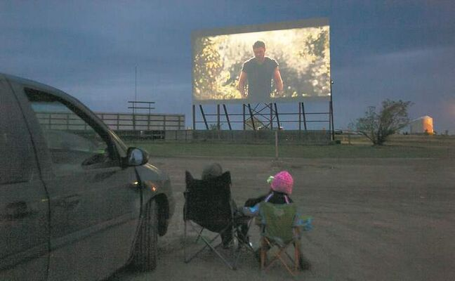 A family watches a film at the Stardust Drive-In in Morden. Operators hope the drive-in experience will make up for the lack of the latest releases.