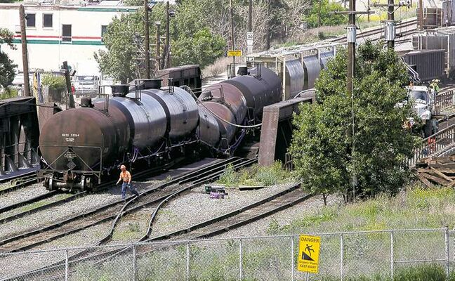 Crews work to stabilize a derailed freight train as it sits on a failing bridge over the Bow River in Calgary on Thursday.