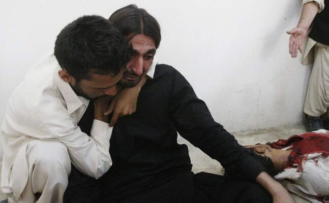 A person comforts a man who mourns the death of a family member who was killed in a bomb blast near a rally by the Awami National Party that killed at least five people, in Quetta, Pakistan. (AP Photo/Arshad Butt)