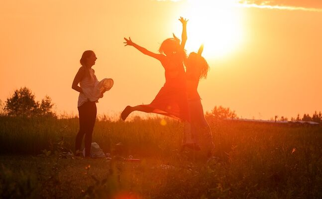 Winnipeg Folk Festival attendees enjoy the sunset and prairie grass at Birds Hill Park.