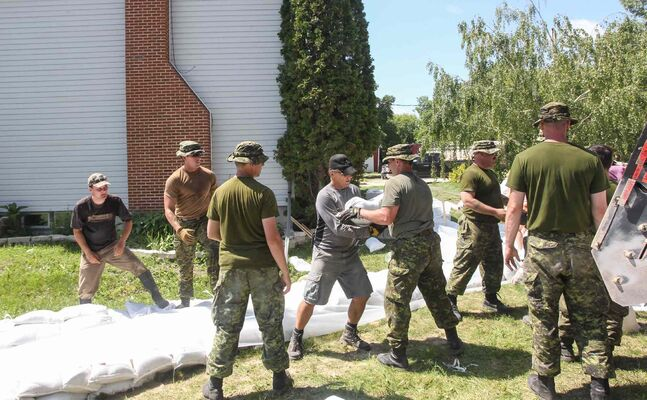 Soldiers from CFB Shilo and volunteers help fortify Kevin Van Camp's home near St. Francois Xavier Sunday afternoon.