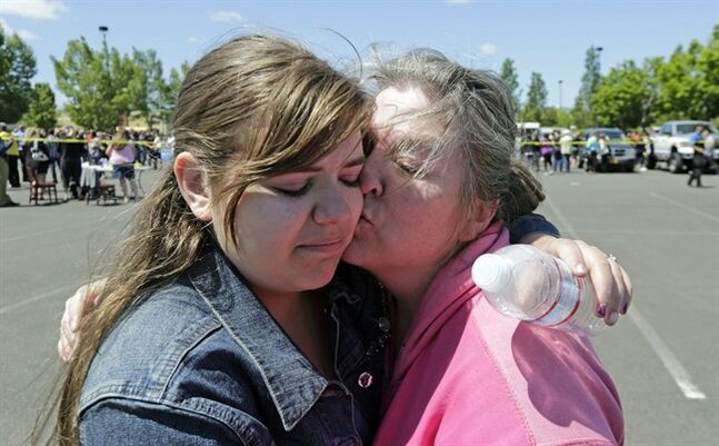 Freshman Britani Iuliano, 15, embraces her mother Wendi Iuliano after students arrived at shopping center parking lot in Wood Village, Ore., after a shooting at Reynolds High School Tuesday, June 10, 2014, in nearby Troutdale. A gunman killed a student at the high school east of Portland Tuesday and the shooter is also dead, police said. (AP Photo/Rick Bowmer)
