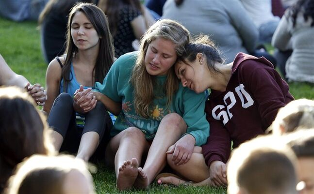 Students from Seattle Pacific University gather outside in a spontaneous prayer circle after a church service was full, following a shooting on the campus of the university Thursday, June 5, 2014, in Seattle. A lone gunman armed with a shotgun opened fire in a building on the campus, killing one person before he was subdued by a student as he tried to reload, police said. Police say the student building monitor at the university disarmed the gunman and several other students held him until police arrived at the Otto Miller building. (AP Photo/Elaine Thompson)