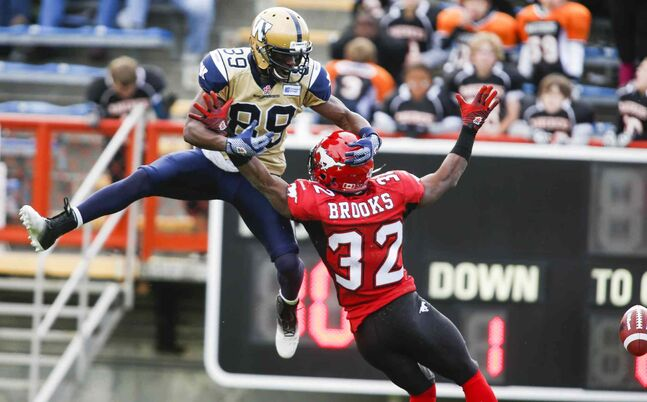 Winnipeg Blue Bombers' Clarence Denmark tries to catch a pass as Calgary Stampeders' Derrius Brooks prevents him from doing so during the first half.