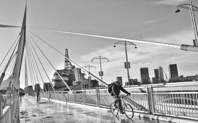 A bicyclist rides over the Esplanade Riel with the partially finished Canadian Museum for Human Rights and downtown Winnipeg in the distance Thursday afternoon.  111124 Mike Deal / Winnipeg Free Press