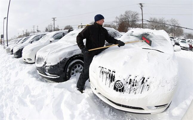 Matt Frame brushes off a Buick at Ray Laethem Buick-GMC in Detroit, Monday, Jan. 6, 2014. Michigan residents are preparing for diving temperatures as they dig out from more than 15 inches of snow in places. Snow wrapped up after starting during the weekend. Roads are slippery, with numerous crashes. In the southern Lower Peninsula, temperatures are to drop late Monday or early Tuesday as low as minus 15. (AP Photo/Paul Sancya)