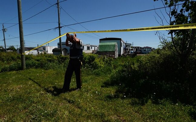 RCMP Const. Doug Baker makes his way from the backyard of the home of shooting suspect Justin Bourque in Moncton, N.B., on Sunday, June 8, 2014. The New Brunswick RCMP are asking the public for any videos or photos they have of the shootings in Moncton that killed three Mounties and injured two others. THE CANADIAN PRESS/Sean Kilpatrick