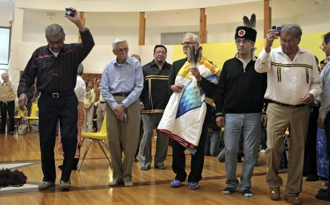 Archbishop James Weisgerber (centre) and his adopted brothers Tobasonakwut Kinew, Bert Fontaine, former Assembly of First Nations national chief Phil Fontaine and Fred Kelly dance around the Thunderbird House after a reconciliation ceremony Saturday.