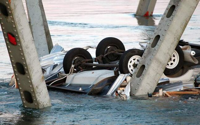 An upside-down vehicle rests in the water after a portion of the Interstate 5 bridge collapsed.