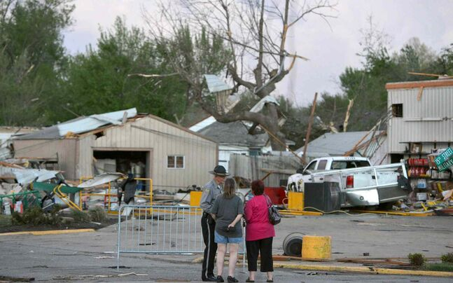 A police officer talks to people at 15th and Military following Sunday's tornado in Baxter Springs, Kan.