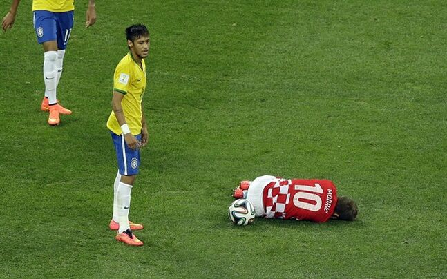 Croatia's Luka Modric, right, sits on the ground after being fouled by Brazil's Neymar, left, during the group A World Cup soccer match between Brazil and Croatia, the opening game of the tournament, in the Itaquerao Stadium in Sao Paulo, Brazil, Thursday, June 12, 2014. (AP Photo/Thanassis Stavrakis)