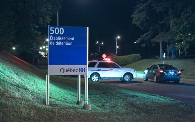 Police cars are shown in front of the Orsainville Detention Centre near Quebec City on Saturday June 7, 2014. There has been another jailbreak in Quebec involving a helicopter. Quebec Provincial Police say three inmates have escaped from the Orsainville Detention Centre. THE CANADIAN PRESS/Francis Vachon.
