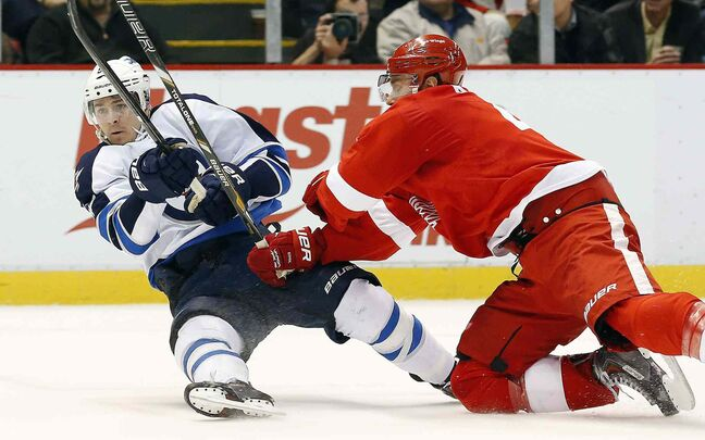 Winnipeg Jets centre Mark Scheifele and Detroit Red Wings defenceman Jakub Kindl collide during the first period.