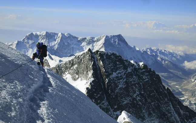 In this file photo released by mountain guide Adrian Ballinger of Alpenglow Expeditions, a climber pauses on the way to the summit of Mount Everest, in the Khumbu region of the Nepal Himalayas. An avalanche swept down a climbing route on Mount Everest early Friday, April 18, 2014, killing at least 12 Nepalese guides and leaving three missing in the deadliest disaster on the world's highest peak.