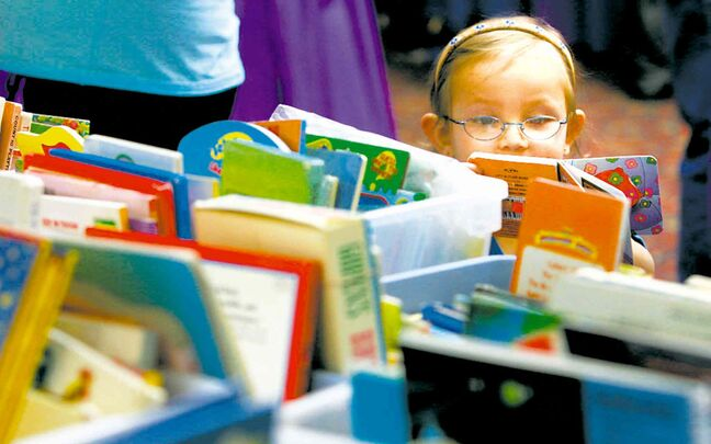In this file photo, Madison McKinney peruses books at a previous market.