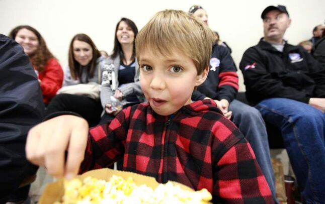 Eight year old Brady Milne enjoys munching on a big bag of popcorn. (Ruth Bonneville/Winnipeg Free Press)