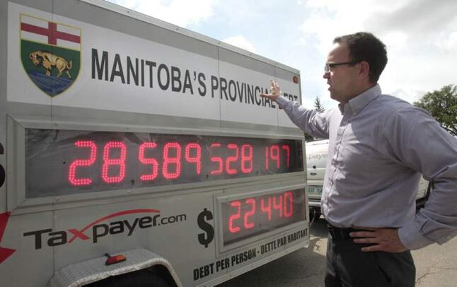 Colin Craig, prairie director with the Canadian Taxpayers Federation, reviews the  'Debt Clock' the group parked in front of the Manitoba Legislative Building Tuesday. The clock shows Manitoba's debt increasing by approximately $6.25 million per day.
