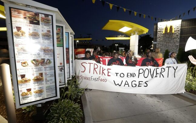 Protesters march on a McDonalds restaurant in Detroit as part of a national protest to push fast-food chains to pay their employees at least $15 an hour Thursday, Sept. 4, 2014. THE CANADIAN PRESS/AP, Paul Sancya