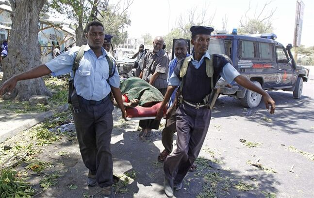 Somali policemen carry a dead body after a suicide bomber blew himself up near a restaurant in Mogadishu, Somalia, Thursday, Feb. 27, 2014. A car bomb blast Thursday in a normally quiet Mogadishu neighborhood blew the facade off a tea shop where intelligence officers are known to congregate, killing at least 11 people, police said. (AP Photo/Farah Abdi Warsameh)