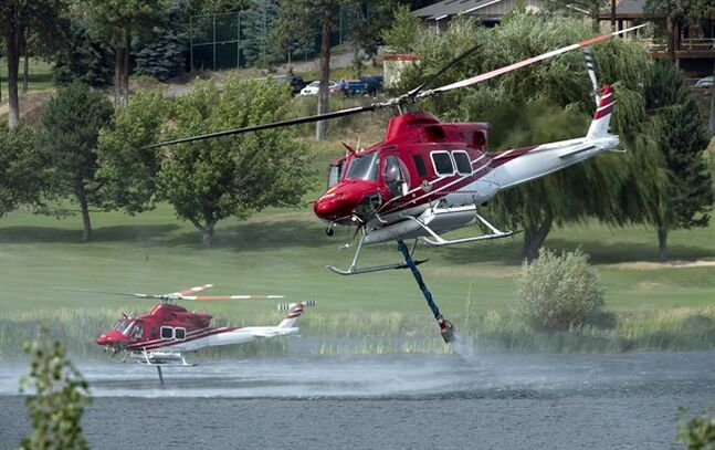 Helicopters get water from Shannon Lake so they can put the water on a blaze on a hillside in West Kelowna, B.C. Friday, July, 18, 2014. Over 2500 residents of the area were evacuated when the fire suddenly grew in size threatening nearby homes. THE CANADIAN PRESS/Jonathan Hayward