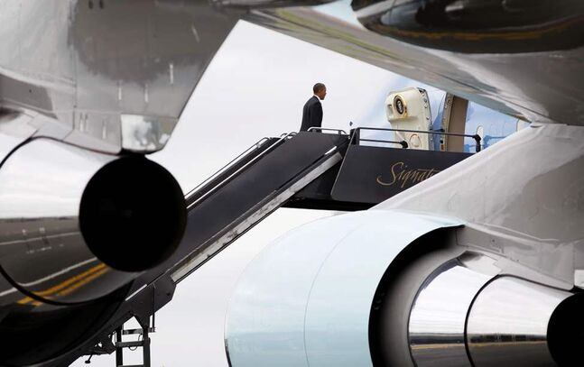 President Barack Obama boards Air Force One at Boston Logan International Airport, en route to Atlanta. (AP Photo/Carolyn Kaster)