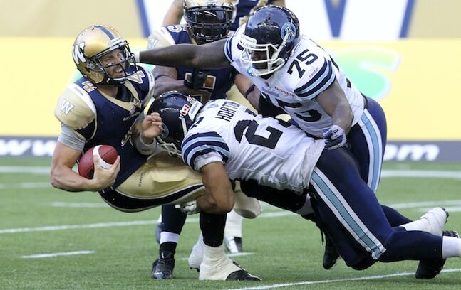 Winnipeg Blue Bombers' quarterback Buck Pierce is sacked by Toronto Argonauts' Shane Horton (27) and Jonathan Williams (75) with less than a minute to go in the first half of Friday night's game.