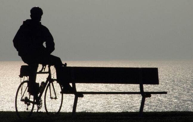 Mark Boksus pauses to look at Lake Michigan in Racine, Wis, Thursday morning May 7, 2009. Boksus commutes to work by bicycle. (AP Photo/Journal Times Mark Hertzberg)