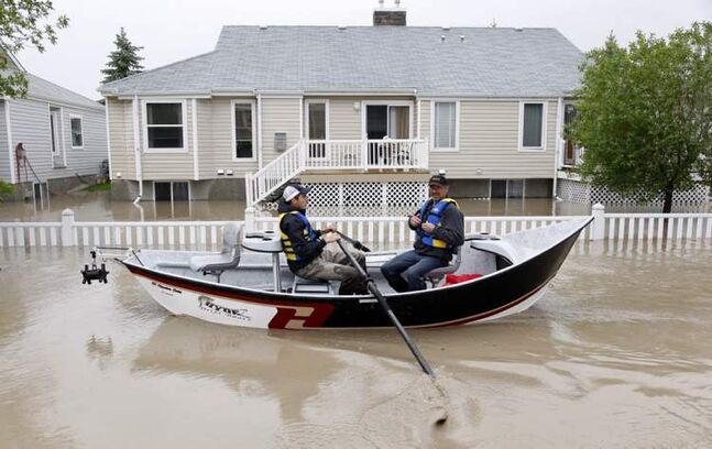 Two men use a fishing boat to rescue residents from a neighborhood after heavy rains caused flooding, closed roads, and forced evacuation in High River, Alta., Thursday.