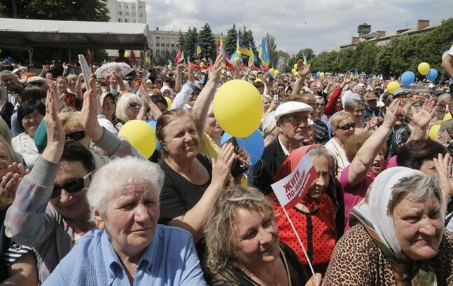 People react during a rally supporting Ukrainian presidential candidate Petro Poroshenko in Uman, Ukraine, Tuesday, May 20, 2014. Presidential vote in Ukraine is scheduled for May 25. (AP Photo/Efrem Lukatsky)