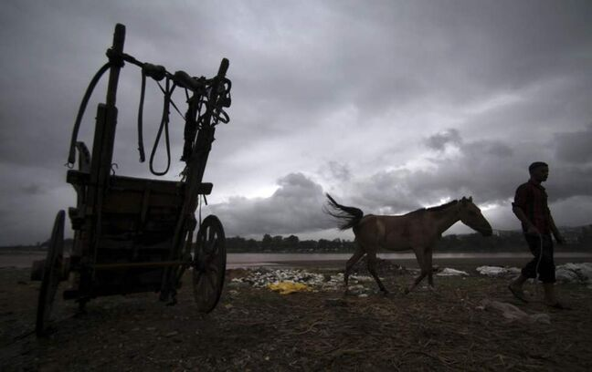 An Indian man walks with his horse as monsoon clouds hover over them in Jammu, India. (AP Photo/Channi Anand)