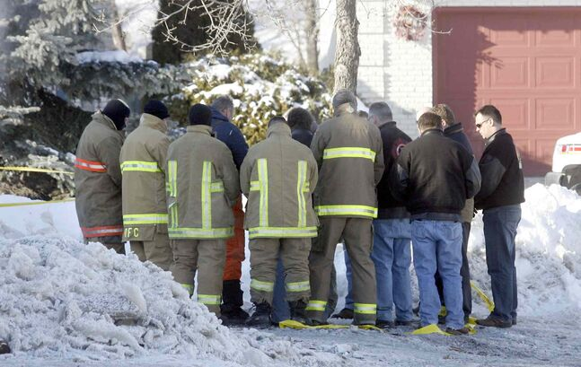 Winnipeg firefighters take a moment after laying memorial wreaths at the site of a February 2007 fire that killed captains Harold Lessard and Tom Nichols. A firefighter traumatized by the event later killed himself.
