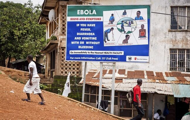 People walk past a billboard encouraging people suffering from symptoms linked to Ebola to present themselves at a health facility for treatment in Freetown, Sierra Leone, Thursday, Aug. 7, 2014. Ethics experts called together by the World Health Organization will meet Monday to discuss whether it is acceptable to use experimental Ebola therapies to treat patients in the ongoing West African outbreak. People familiar with the various treatment options say, though, that in the near term the discussion is pretty well moot -- there aren't supplies of drugs or vaccines to give. THE CANADIAN PRESS/AP-Michael Duff
