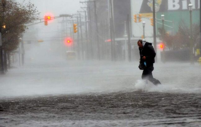 Michael Wirtz, of Wilmington, Del., braves flood waters and high winds that arrived with Hurricane Sandy along North Michigan Avenue in Atlantic City, N.J. (AP Photo/The Press of Atlantic City, Michael Ein)