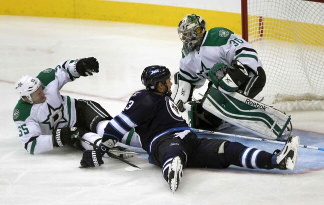 Dustin Byfuglien slides into the net and goaltender Dan Ellis after Sergei Gonchar of the Dallas Stars tripped him up during the third period.
