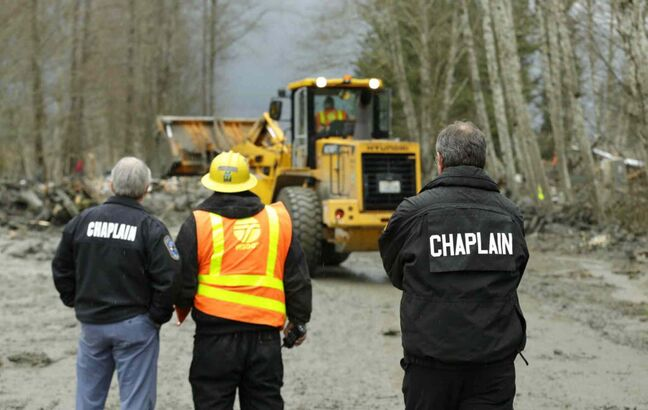 Washington State Patrol chaplains Joel Smith, left, and Mike Neil, right, watch as workers using heavy equipment work to clear debris, Tuesday, March 25, from Washington Highway 530 on the western edge of the massive mudslide that struck near Arlington, Wash. Saturday, killing at least 16 people and leaving dozens missing.