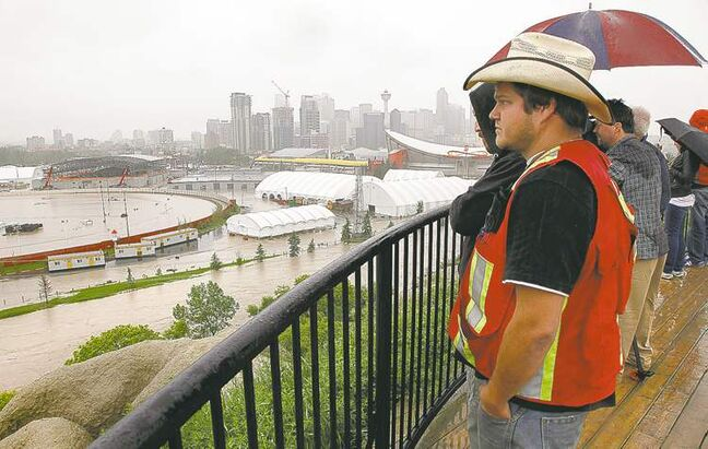 Calgarians look out over the flooded Calgary Stampede grounds and Saddledome  on Friday. More rain was forecast for Friday and today.