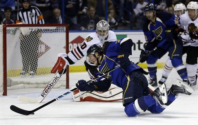 St. Louis Blues' T.J. Oshie, front, reaches for a puck to score past Chicago Blackhawks goalie Corey Crawford during the second period in Game 5 of a first-round NHL hockey playoff series Friday, April 25, 2014, in St. Louis. (AP Photo/Jeff Roberson)