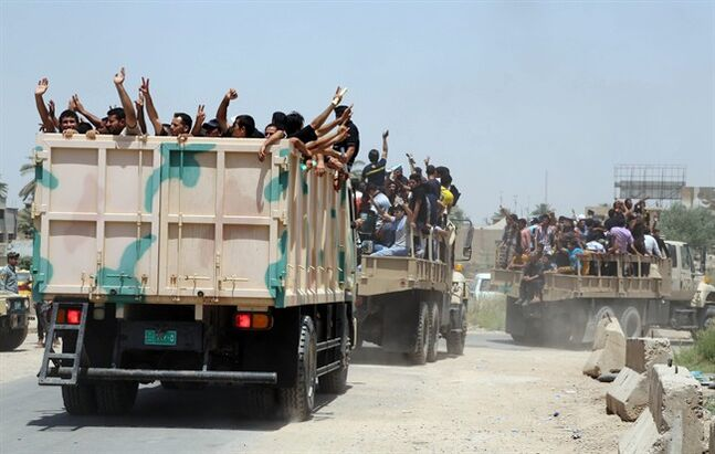 Iraqi men fill military trucks to join the Iraqi army at the main recruiting center in Baghdad, Iraq, Saturday, June. 14, 2014, after authorities urged Iraqis to help battle insurgents. Hundreds of young Iraqi men gripped by religious and nationalistic fervor streamed into volunteer centers across Baghdad Saturday, answering a call by the country's top Shiite cleric to join the fight against Sunni militants advancing in the north.(AP Photo/Karim Kadim)