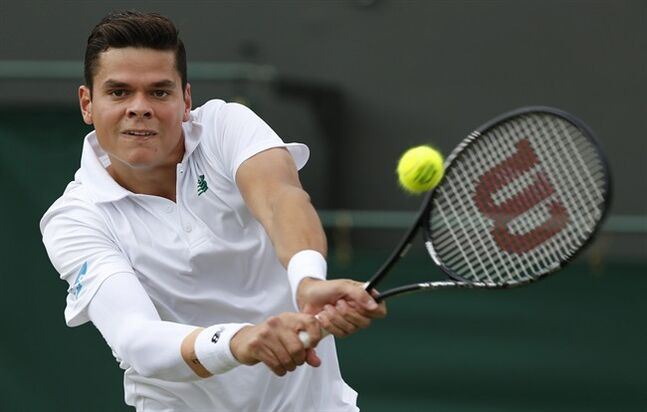 Milos Raonic of Canada plays a return to Kei Nishikori of Japan during their men's singles match at the All England Lawn Tennis Championships in Wimbledon, London, Tuesday, July 1, 2014. (AP Photo/Sang Tan)