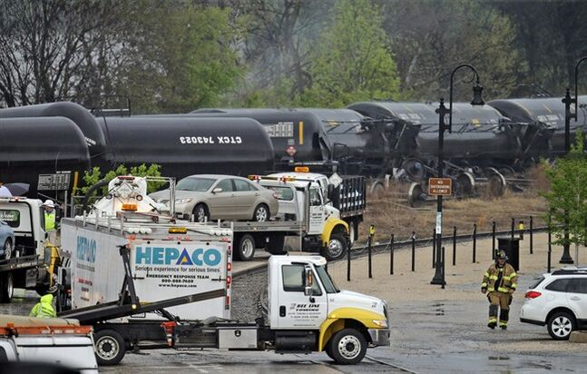 Firefighters and rescue workers work along the tracks where several CSX tanker cars carrying crude oil derailed and caught fire along the James River in Lynchburg, Va.., Wednesday, April 30, 2014. Police said that over a dozen tanker cars were involved in the derailment. (AP Photo/Steve Helber)
