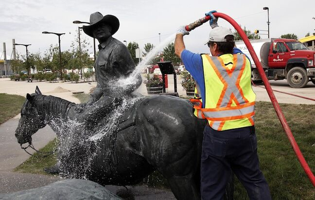 A clean-up crew member hoses down a statue at the Calgary Stampede grounds Monday. Stampede officials say the 2013 event is a go.