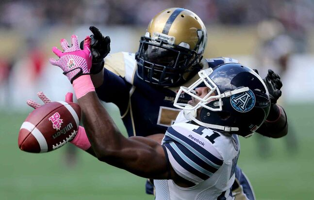 Winnipeg Blue Bombers' Demond Washington (7) interferes with Toronto Argonauts' Dontrelle Inman (11) in the end zone during the first half.