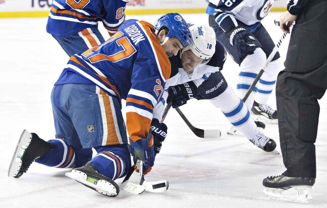 Winnipeg Jets' Bryan Little (18) and Edmonton Oilers' Boyd Gordon (27) battle in the face-off circle during first period NHL hockey action in Edmonton, Alta., on Monday.