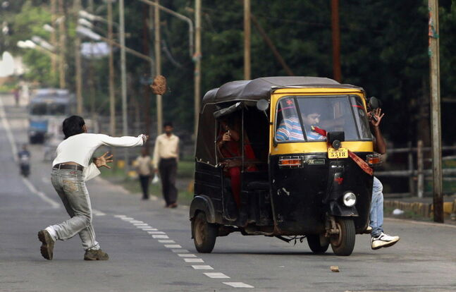 An activist of the ruling Congress party throws a stone at an auto-rickshaw during a statewide strike to protest against the clashes between police and the party workers during a rally last week in Bhubaneswar, India. Many protestors were taken into custody for picketing near government offices and other places during the strike, according to local reports. (AP Photo/Biswaranjan Rout)