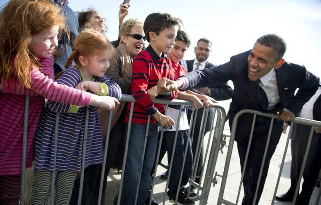 President Barack Obama reaches to shake hands with children as he arrives at John F. Kennedy International Airport, Thursday, Oct. 18, 2012, in New York. (AP Photo/Carolyn Kaster)