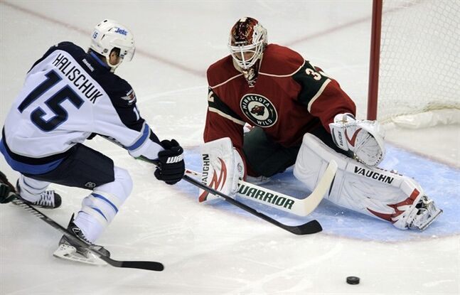 Minnesota Wild goalie Niklas Backstrom, right, stops the shot of Winnigeg Jets' Matt Halischuk (15) in the first period of an NHL hockey game on Saturday, Sept. 21, 2013, in St. Paul, Minn. (AP Photo/Tom Olmscheid)