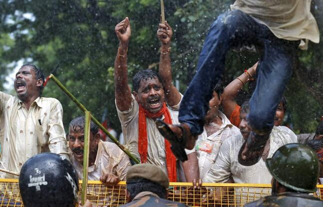 Supporters of India's main opposition Bharatiya Janata Party (BJP) shout slogans as police use a water cannon to disperse them during a demonstration in favor of carving a separate state of Telangana from Andhra Pradesh state, in New Delhi, India. Supporters of the new Telengana state have complained their area in the north was underdeveloped and ignored by powerful politicians from southern Andhra Pradesh. Demands for a separate state have erupted sporadically since the 1950s. (AP Photo/Saurabh Das)
